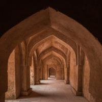 Mandu India, afghan ruins of islam kingdom, palace interior, mosque monument and muslim tomb. Sunshine from door in dark corridor.